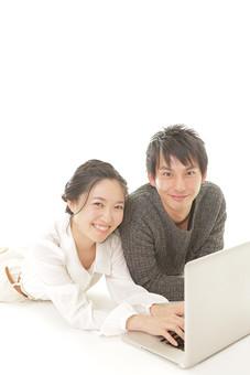 人物 男性 男子 女性 女子 若い デート カップル アベック 夫婦 新婚 白バック 白背景 部屋 リビング くつろぐ リラックス 仲良し 寝転ぶ パソコン 情報 検索 情報端末 インターネット 画面 日本人 WEBサイト mdjm008 mdjf026