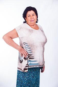 人物 女性 外国人 外人 外国人女性 外人女性 中年 熟年 年配者 50代 60代 中年太り 肥満 ぽっちゃり 肥満女性 白バック 上半身 腰に手を当てる ポートレート 黒髪 イヤリング アクセサリー ブレスレット おしゃれ オシャレ ブラウス スカート  シニア mdfs011