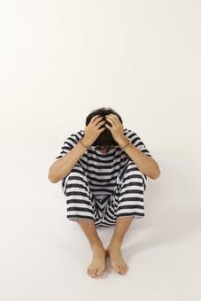 人物 男性 囚人 囚人服 逮捕 捕まる 犯罪 犯人 犯罪者 容疑者 ボーダー ストライプ 縞々 留置所 留置場 牢獄 牢屋 頭を抱える 後悔 反省 過ち 罪 全身 座る 正面 白バック 白背景