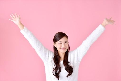 人物 女性 日本人 若者 若い  20代 美人 かわいい ロングヘア カジュアル  ラフ 私服 セーター ニット 屋内  スタジオ撮影 背景 ピンク ピンクバック ポーズ  おすすめ 両手 広げる 万歳 バンザイ 喜び うれしい 嬉しい やったー mdjf007