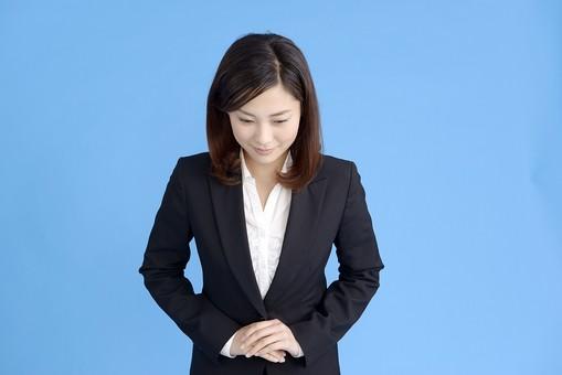 人物 女性 日本人 20代 若者  ビジネス スーツ 黒 紺色 セミロング  OL 社会人 会社員 ビジネスマン 就活  就職活動 真面目 ポーズ 屋内 スタジオ撮影  ブルーバック 上半身 正面 お辞儀 頭を下げる お礼 挨拶 微笑む  mdjf013