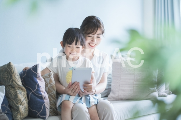 ソファに座ってオンラインコミュニケーションをする親子の写真