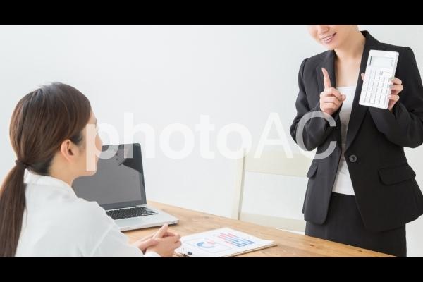 電卓を見て喜ぶ女性の写真