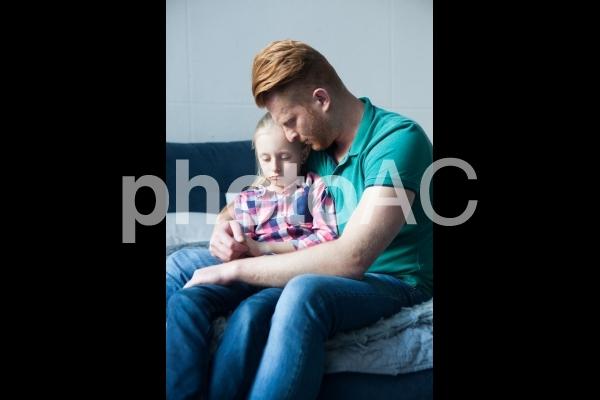 落ち込む娘を抱っこするお父さん2の写真