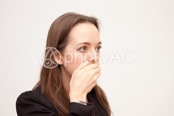 口を押さえて目を見開く女性の写真