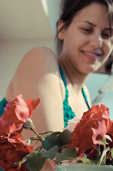 外国 海外 屋内 屋外 人物 1人 外国人 白人 セルビア人 大人 若い 女性 女 女の子 胸から上 ブルネット 黒髪 セミロング まとめ髪 ひっつめ髪 無造作ヘア 空 陽射 植物 造花 薔薇 バラ ばら 赤 ピンク 花 葉 ベランダ バルコニー 微笑み 微笑 笑顔 笑う 香る アップ 後ボケ mdff021