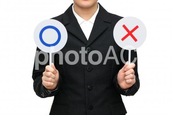 ○と×を持つ女性の写真
