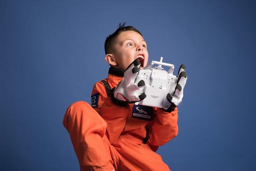 背景 ダーク ネイビー 紺 男の子 男子 男児 男 子ども こども 子供 1人 ひとり 一人 児童 宇宙服 宇宙 服 スペース スペースシャトル 宇宙飛行士 飛行士 オレンジ 希望 夢 将来 未来 体験 職業体験 職業 小道具 小物 おもちゃ コントローラー リモコン コントロール 座る 腰かける 驚く びっくり ビックリ 衝撃 焦る 躍動感 外国人  mdmk009