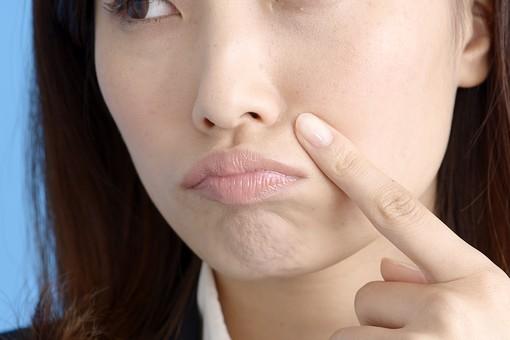 人物 女性 日本人 20代 若者  ビジネス  セミロング  OL 社会人 会社員 ビジネスマン  真面目 ポーズ 屋内 スタジオ撮影  ブルーバック クローズアップ 鏡 美容 顔 肌 肌荒れ ニキビ にきび 吹き出物 気になる 指 押さえる 憂鬱  mdjf013 豊麗線 ほうれい線 悩み