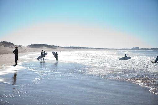 リゾート 自然 風景 スポーツ 人物 立つ  アウトドア サーフィン サーフボード サーファー   ウェット ドライスーツ  ラッシュガード マリンスポーツ ボード 板 レジャー 遊び   海 波 白波  海岸 波打ち際 砂 砂浜 ビーチ  水際  空 晴天 夏 フレア 反射  全身    外国 海外
