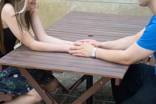 屋外 人物 外国人 女性 男性 大人 2人 若い 若者 20代 カップル 夫婦 ペア 恋人 リラックス 愛情 接近 触れる 触れ合う  笑顔 話す 会話 甘える テーブル 座る 手 重ねる LOVE 愛してる 好き 願望 願い お願い ボディタッチ 手元 腕時計 デート ラブラブ mdff023 mdfm013