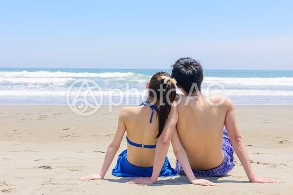 海を見つめ寄り添う二人の男女の写真