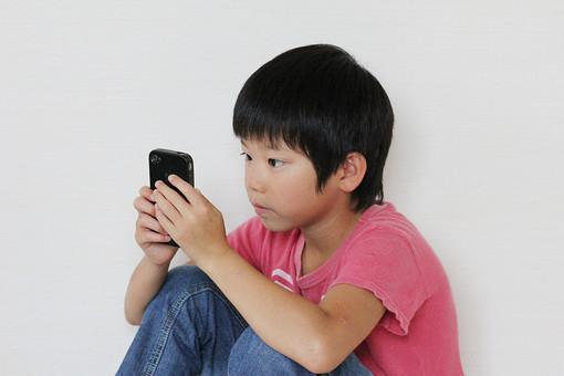 子供 人物 男の子 小学生 真剣 遊ぶ スマホ スマートフォン 日本人 男子 こども キッズモデル 正面 室内 屋内 白バック 白背景 上半身 ゲーム アプリ 熱中 夢中 集中 依存 ネット マナー 道徳 教育 mdmk026
