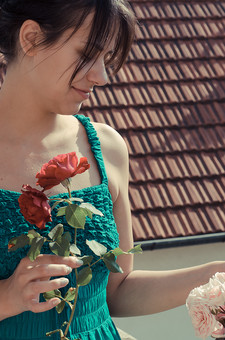 外国 海外 屋内 屋外 人物 1人 外国人 白人 セルビア人 大人 若い 女性 女 女の子 上半身 ブルネット 黒髪 セミロング まとめ髪 ひっつめ髪 無造作ヘア 空 陽射 植物 造花 薔薇 バラ ばら 赤 ピンク 花 葉 ベランダ バルコニー 屋根 屋根材 微笑み 微笑 笑顔 香り 嗅ぐ 匂う アップ mdff021