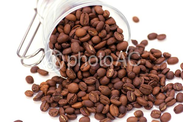 カップから溢れる珈琲豆の写真