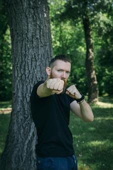 人物写真 ポートレート ポートレイト 人物 人 人間 外国人  男性 白人男性  フィットネス 運動 健康 ストレッチ アウトドア 手 両手 筋トレ 木 森林 林 葉 Tシャツ 拳 握る ストレート 突く ボクシング mdfm006