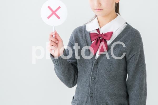 バツを持つ制服を着た女の子の写真