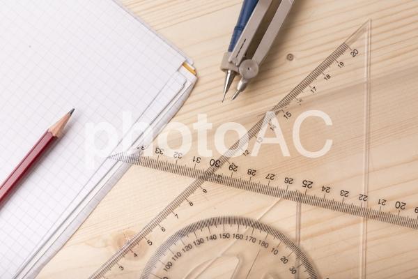 鉛筆と分度器と三角定規とコンパスとノート2の写真