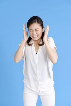 女性 ポーズ 人物 30代 日本人 黒髪 爽やか カジュアル 屋内 正面 ブルーバック 青背景 半そで 白  怒り 怒る  腹立たしい 両手 耳元 上半身 忍耐 耐える 耐え忍ぶ いらいら 聞く耳持たず 聞きたくない うるさい 頭痛 やめて 耳 塞ぐ がまん 我慢 目 瞑る mdjf013