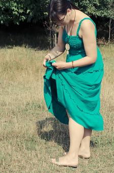 外国 海外 屋外 野外 自然 人物 1人 外国人 白人 セルビア人 大人 若い 女性 女 女の子 横向き ブルネット 黒髪 セミロング まとめ髪 ひっつめ髪 無造作ヘア 普段着 青緑の服 ワンピース ロングワンピース ノースリーブ キャミソールワンピース ネックレス ペンダント レザーコード ブレスレット アクセサリー 眼鏡 メガネ めがね 裸足 はだし すね つま先 植え込み 低木 木 木立 芝生  シミ 汚れ ほつれ 確認 mdff021
