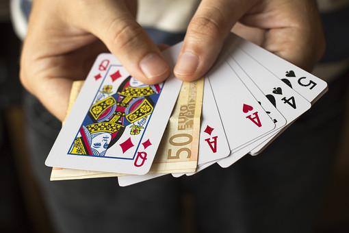 トランプ カード ゲーム 札 娯楽 屋内 手品 マジック 遊び  並べる   重ねる 配る 切る カードゲーム 人物 手 両手 指 持つ 男性 爪 広げる 器用 赤 黒 手元 アップ 揃う 並ぶ 絵札 札 お金 お札 紙幣 賭ける 賭け Q A クイーン エース ダイヤ ハート ギャンブル