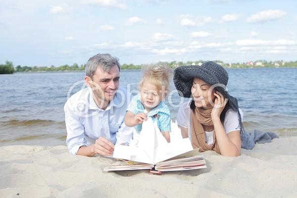 砂浜で絵本を読む家族3の写真