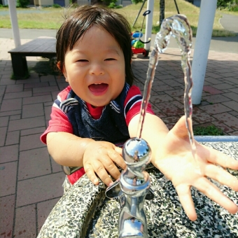 公園の水飲み場で遊ぶ子供の写真