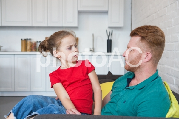 機嫌の悪い娘を膝に乗せているお父さん1の写真