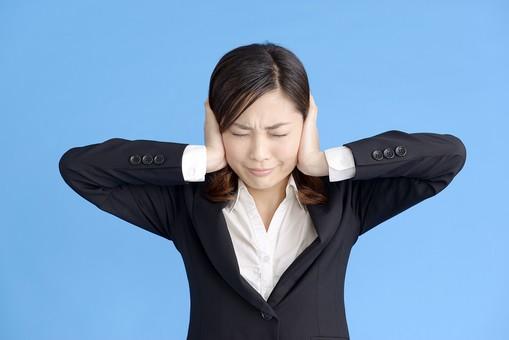 人物 女性 日本人 20代 若者  ビジネス スーツ 黒 紺色 セミロング  OL 社会人 会社員 ビジネスマン 就活  就職活動 真面目 ポーズ 屋内 スタジオ撮影  ブルーバック 上半身 耳を塞ぐ うるさい 騒音 雑音 聞かない 聞こえない シャットアウト 無視 mdjf013