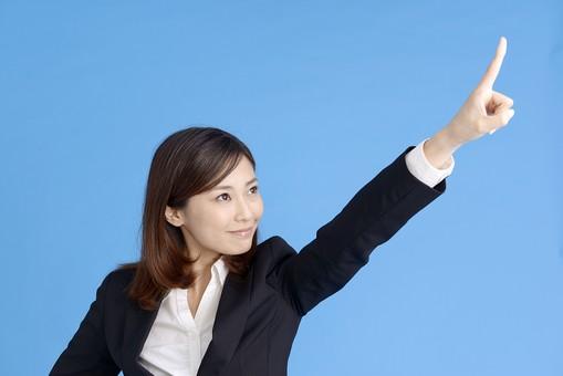 人物 女性 日本人 20代 若者  ビジネス スーツ 黒 紺色 セミロング  OL 社会人 会社員 ビジネスマン 就活  就職活動 真面目 ポーズ 屋内 スタジオ撮影  ブルーバック 上半身 指差し 指さす 上 目指す 示す 目標 注目 ポイント 笑顔 mdjf013