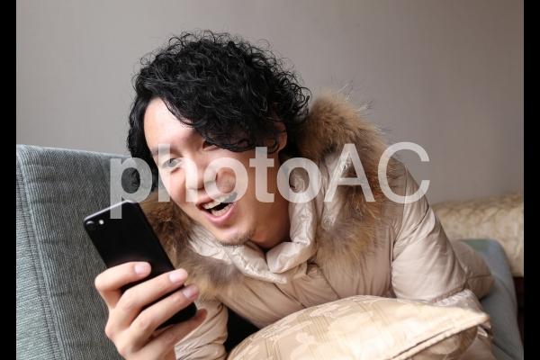 スマホを見て熱狂する男性の写真