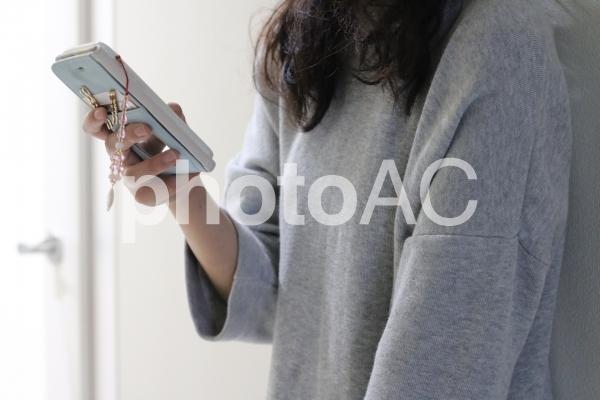 スマホを操作する女性の手の写真
