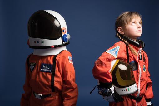 背景 ダーク ネイビー 紺 子ども こども 子供 2人 ふたり 二人 男 男児 男の子 女 女児 女の子 児童 宇宙服 宇宙 服 スペース スペースシャトル 宇宙飛行士 飛行士 オレンジ 希望 夢 将来 未来 体験 職業体験 職業 小道具 小物  ヘルメット 被る かぶる 抱える 見上げる 横顔 目指す 外国人  mdmk009 mdfk045