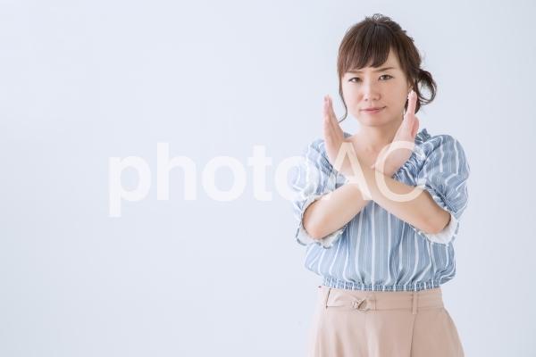 バツのジェスチャーをする女性の写真