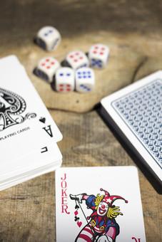 トランプ カード ゲーム 札 娯楽 木 屋外 茶色 机 テーブル 赤 青 裏側 裏 絵札 黒 木目 手品 マジック 遊び 絵札 乱雑 サイコロ  重ねる 配る 切る カードゲーム A エース 1 スペード ジョーカー ババ JOKER ピエロ