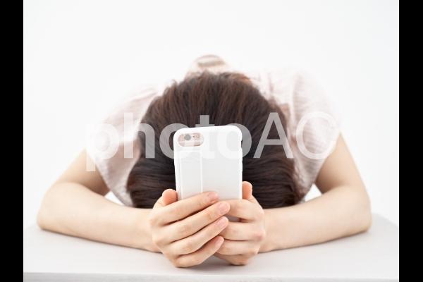 スマホを持ってがっかりする女性の写真