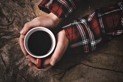 コーヒー 珈琲 カフェ コーヒーカップ カップ コップ 茶色 飲み物 ドリンク 手 両手 持つ 包む 温める 置く ボディーパーツ ハンドパーツ テーブル 木目 長袖 チェック 真上 コーヒータイム 休憩 休息 リラックス
