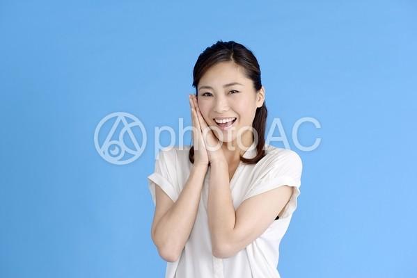 手を合わせ喜ぶ女性1の写真