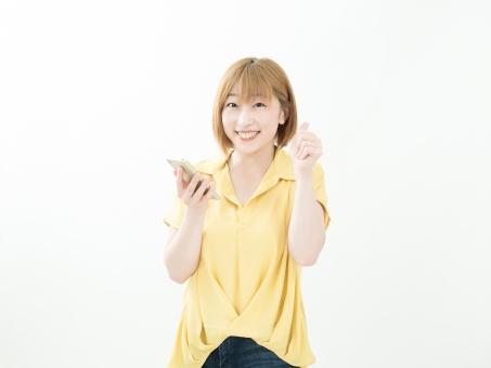 スマホを持つ女性 笑顔でグッドサインの写真