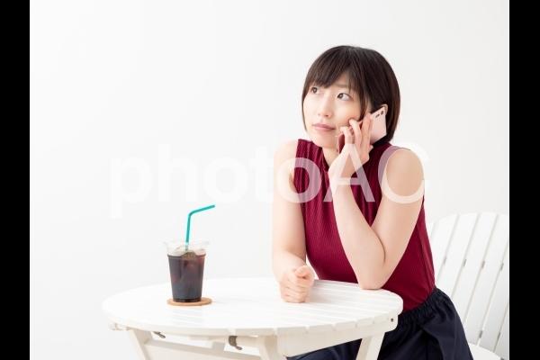 カフェでスマホを見る女性のイメージの写真