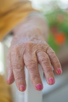 人物 老人 お年寄り 高齢者 シルバー   年老いた手 ハンドパーツ 手 指 ハンド   パーツ 手の表情 年老いた手 皺 しわ   シワ クローズアップ 女性 おばあちゃん おばあさん 爪 ネイル マニキュア 赤 ピンク おしゃれ お洒落 いす イス 椅子 ひじ掛け 肘掛け 座る 片手 正面 手元 手先 指先