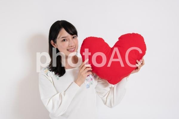ハートを持って笑顔の女性の写真
