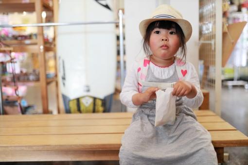 ベンチでお菓子を食べる女の子1の写真
