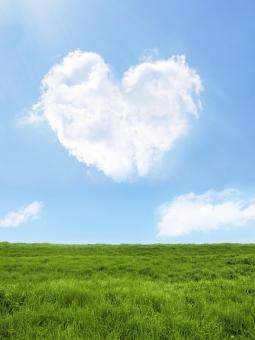 ハート型の雲と青空と草原-縦長構図の写真