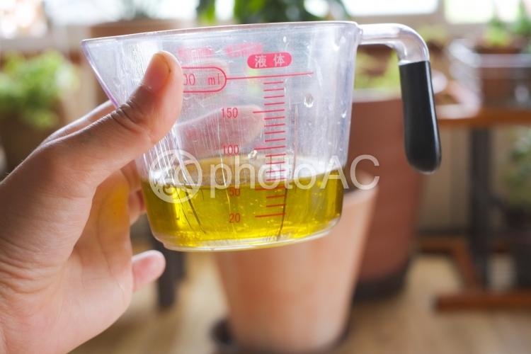 計量カップで油を計るの写真