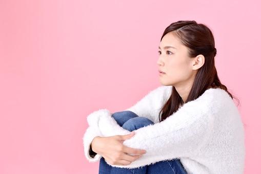 人物 女性 日本人 若者 若い  20代 美人 かわいい ロングヘア カジュアル  ラフ 私服 セーター ニット 屋内  スタジオ撮影 背景 ピンク ピンクバック ポーズ  おすすめ 膝を抱える 座る 横向き 横顔 体育座り 体操座り 見つめる 考え事 考える mdjf007