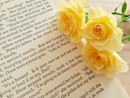 洋書と黄色いバラの写真