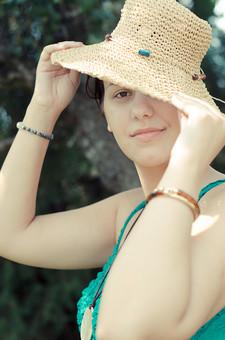 外国 海外 屋外 野外 自然 人物 1人 外国人 白人 セルビア人 大人 若い 女性 女 女の子 胸から上 ブルネット 黒髪 セミロング まとめ髪 ひっつめ髪 無造作ヘア 普段着 青緑の服 ノースリーブ キャミソール ネックレス ペンダント レザーコード ブレスレット アクセサリー 帽子 麦わら帽子 木 微笑む 微笑 笑顔 見つめる 目を合わせる かぶる mdff021