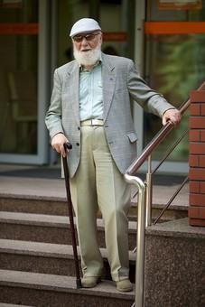 病院 医院 診療所 屋外 外 玄関 エントランス 階段 入口 外国人 白人 男性 老人 高齢 高齢者 おじいさん おじいちゃん 髭 ヒゲ ひげ 白髪 ハンチング帽 上着 ジャケット 立つ 下りる 手すり 杖 つえ サングラス 全身 mdjms016