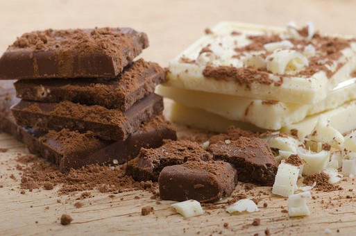 御菓子 お菓子 洋菓子 スイーツ チョコ チョコレート ショコラ チョコ菓子 チョコレート菓子 甘味  板チョコ 板チョコレート 粉 粉末 カカオ ホワイトチョコ ホワイトチョコレート 積む 積みかさねる 上に置く重ね合わせる 重ねる 重なる  振りかける ふりかける 振りかけた ふりかけた シナモンパウダー ココアパウダー 割る 欠片 かけら